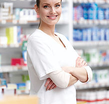 Portrait of confident young pharmacist with arms crossed at drugstore
